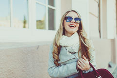 Happy and cheerful, smiling Blond in sunglasses young model or student in light coat on the natural street background outside. Stock Photography