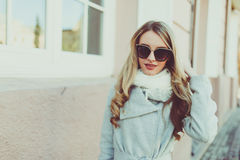 Happy and cheerful, smiling Blond in sunglasses young model or student in light coat on the natural street background outside. Royalty Free Stock Photos