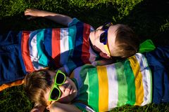 Happy cheerful smiling children, laying on a grass, wearing sunglasses, smiling at the camera, shot from above stock images