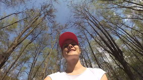 Happy cheerful smiling young woman cycling under trees in sunny park. POV Action Camera. Happy cheerful smiling woman in white t-shirt riding bike under trees in stock video