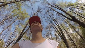 Happy cheerful smiling young woman cycling under trees in sunny park. POV Action Camera. Happy cheerful smiling woman in white t-shirt riding bike under trees in stock footage