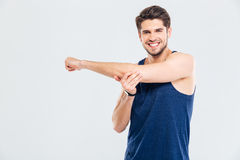 Happy cheerful sportsman doing stretching exercises. Happy cheerful young sportsman doing stretching exercises isolated on a gray background Royalty Free Stock Images