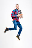 Happy cheerful student with backpack holding books and jumping. Full length of happy cheerful young student in plaid shirt and jeans with backpack holding books Stock Image