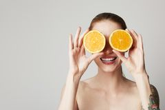 Happy cheerful tattoed young woman is holding two halves of an orange fruit in front of her eyes. Happy cheerful tattoed young woman is holding two halves of an royalty free stock photos