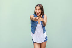 Happy cheerful teenage girl with freckles, casual style clothes, looking and pointing fingers at camera indoors. Studio shot, light green background stock images