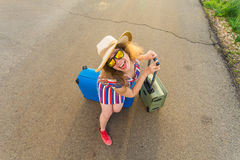 Happy cheerful traveler woman standing with suitcases on the road and smiling. Concept of travel, holidays, journey Stock Photography