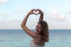 Woman in honeymoon frames hand into heart shape, finger heart frame. looking and smiling to the camera stock photo