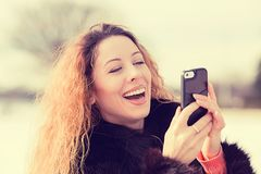 Happy, cheerful woman excited by what she sees on cell phone Royalty Free Stock Images