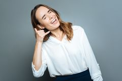 Happy cheerful woman pretending to make a call. Imaginary conversation. Happy cheerful emotional woman holding her hand near the ear and pretending to make a Stock Image