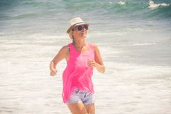 Happy cheerful woman running along the beach against the ocean.  stock images