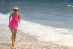 Happy cheerful woman running along the beach against the ocean.  royalty free stock photo