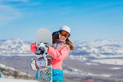 Happy cheerful woman in a ski suit and glasses holding a snowboard in her hands in the winter in the mountains Extreme winter. Sports. Smiling snowboarder stock photo