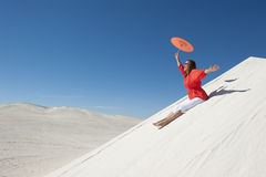 Happy and cheerful woman sliding down sand dune Royalty Free Stock Images