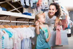 Happy cheerful woman with small child choosing clothes. Happy cheerful women with small child choosing clothes in kids apparel boutique Royalty Free Stock Image