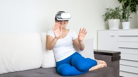 Happy cheerful woman watching movie in VR headset on sofa. Cheerful woman watching movie in VR headset on sofa Royalty Free Stock Photography