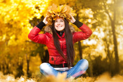 Happy cheerful woman in a wreath of autumn leaves Royalty Free Stock Photos