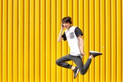Happy, funny student man jumping with headphones on a yellow wall background. Teen lifestyle concept. Copy space. royalty free stock photography
