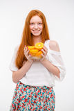 Happy cheerful young female holding oranges in glass bowl royalty free stock images
