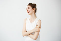 Happy cheerful young girl with bun smiling laughing over white background. Crossed arms. Stock Photography