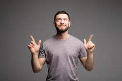 Happy cheerful young guy gesturing up with fingers on grey Stock Photos