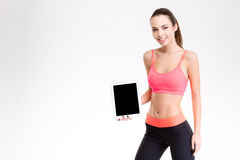 Happy cheerful young sportswoman showing tablet pc blank screen Royalty Free Stock Photos