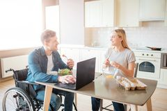 Happy cheerful young student with disability and inclusiveness eating salad and studying. He look at woman and smile stock image