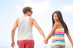 Happy cheerful young trendy couple holding hands Royalty Free Stock Image