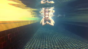 Happy cheerful young woman in blue swimming suite in swimming pool, underwater view. Action camera. Happy cheerful young woman in blue swimming suite and glasses stock video