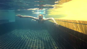 Happy cheerful young woman in blue swimming suite in swimming pool, underwater view. Action camera. Happy cheerful young woman in blue swimming suite and glasses stock footage
