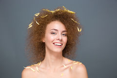 Happy cheerful young woman with petals on hair and shoulders Stock Photo