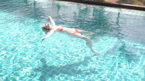 Happy cheerful young woman in red swimming suite lying on water in swimming pool. Beautiful sunny day stock video