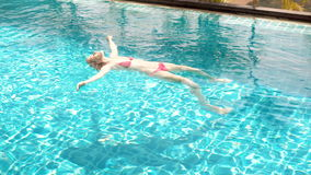 Happy cheerful young woman in red swimming suite lying on water in swimming pool. Beautiful sunny day stock footage