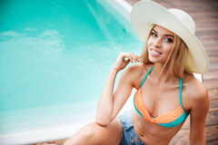 Happy cheerful young woman sitting near swiming pool. Happy cheerful young woman in hat with blonde hair sitting near swiming pool Royalty Free Stock Photo