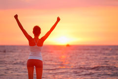 Happy cheering celebrating success woman sunset. Happy cheering celebrating success woman at beautiful beach sunset. Fitness girl enjoying view with arms raised stock image