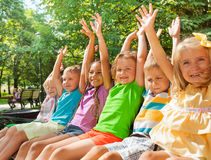 Happy cheering kids lifting hands on the bench Royalty Free Stock Photo