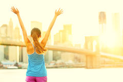 Happy cheering woman in New York City. Enjoying view and sun on Brooklyn Bridge. Fit female fitness runner joyful and excited after running Stock Image