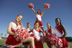 Happy Cheerleaders Holding Pompoms On Field stock image