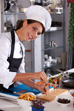 Happy chef. Laughing female chef preparing a small amuse on a stick Royalty Free Stock Image