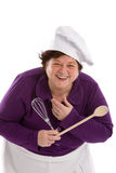 Happy chef. Woman holding a wooden spoon and a mixer and laughing on white Royalty Free Stock Image