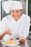 Happy Chef Adding Spices To Food. Portrait of happy female chef adding spices to food at commercial kitchen counter Royalty Free Stock Photography