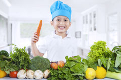 Happy chef boy with fresh vegetables. Happy chef boy holding a carrot with fresh vegetables at home royalty free stock photography
