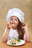 Happy chef child eating a creative pasta dish Stock Images
