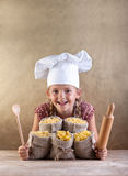 Happy chef child with pasta assortment. Happy laughing chef child with pasta assortment in burlap bags and kitchen utensils - traditional food Royalty Free Stock Photos