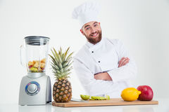 Happy chef cook standing with arms folded. Portrait of a happy chef cook standing with arms folded near table with fruits isolated on a white background stock photo