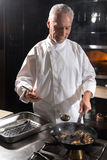 Happy chef cooking mushrooms on the frying pan Royalty Free Stock Photography
