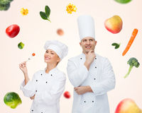 Happy chef couple or cooks over food background Stock Photo