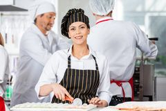 Happy Chef Cutting Ravioli Pasta With Colleagues Stock Photos