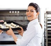 Happy Chef Giving Baking Sheet To Colleague By Royalty Free Stock Photos