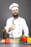 Happy chef holding a big sharp knife on a board ready to cook. Over gray background Royalty Free Stock Photo