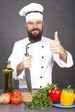 Happy chef holding a big sharp knife and showing thumb up ready. To cook over gray background Stock Photography